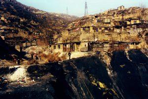 Gujiao, ville minière. Le salaire des ouvriers migrants ne leur permet pas de se construire une vraie maison au bord du       « trou ».Dans les bidonvilles à l'air charbonneux, sans eau courante ni protection sociale, les maladies respiratoires prolifèrent et les maisons s'effondrent une à une, fragilisées par les galeries qui rongent la montagne de l'intérieur.