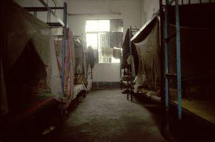 Dortoirs de l'usine Ming Sheng. 12 lits, 20 mètres carrés. Une douche et deux toilettes pour 50 personnes. Les ouvrières doivent payer eau et électricité en plus du prix de leur lit. Elles sont obligées de dormir là, moyennant un tiers de leur salaire, car les usines n'aiment pas la dispersion des employés.