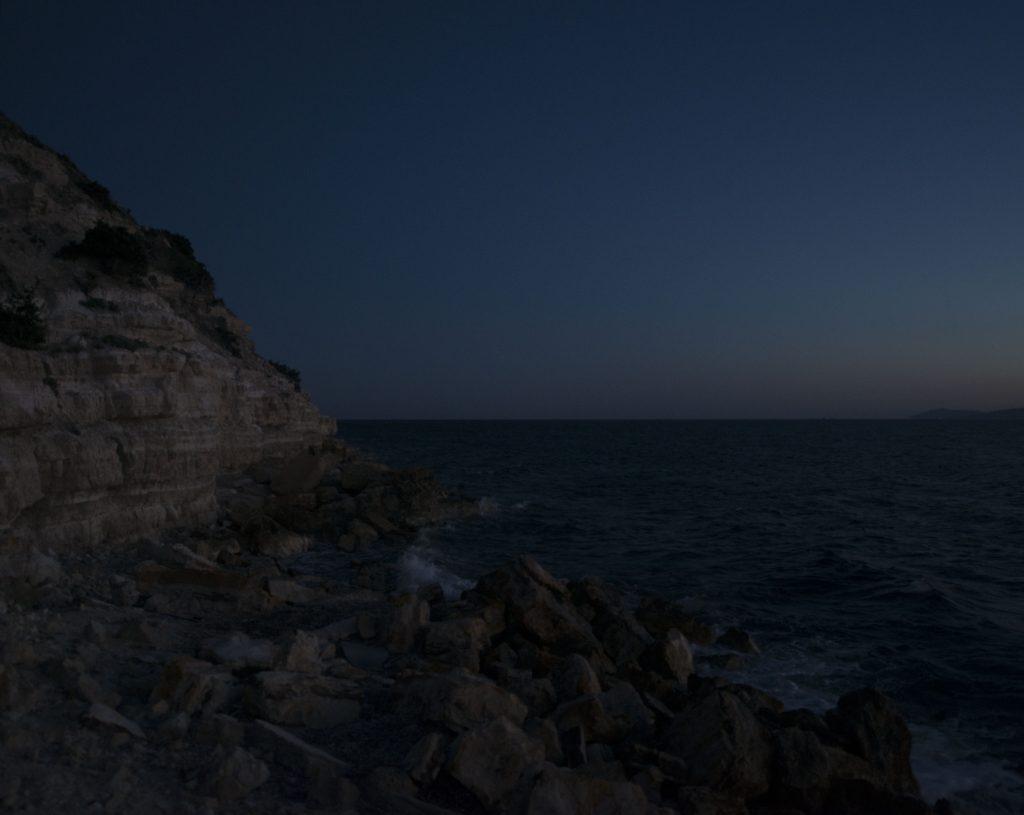 L'accès à la mer se fait la nuit, au pied de la falaise, au milieu des rochers frappés par la mer démontée. Embarquer dans l'urgence sur les frêles canots malmenés par le ressac. À la moindre réticence, les passeurs forcent, sous la menace de leur arme, des hommes, des femmes, des enfants, terrorisés, à s'entasser sur les rafiots de fortune.  Saïd, un réfugié syrien, a payé 10 000 dollars pour traverser avec sa femme et ses six enfants. Le passeur avait garanti qu'ils seraient seuls sur le bateau et lorsqu'il a découvert l'embarcation bondée, Saïd a protesté. Menacé par le fusil du passeur, il a fini par embarquer. Lorsque le canot a chaviré, il est le seul à avoir survécu. Sa femme et ses enfants sont morts noyés. La nuit dans la mer Égée. Le bras de mer de quelques kilomètres est devenu un cimetière de réfugiés. «Les douaniers grecs sont arrivés en bateau et il cognaient le nôtre en disant: «Go back, go back!». En nous cognant ils ont fait un trou dans la coque. Tout le monde criait et pleurait: «Il y a de l'eau! il y a de l'eau!» Le bateau s'est retourné. J'ai réussi à sortir mon fils et ma femme de la cabine, mais les autres sont restés coincés. Onze personnes, dont huit enfants. Le bateau a coulé avec les familles à l'intérieur. Dans l'eau, je tenais mon fils et j'ai demandé de l'aide à la police. Je leur ai tendu mon enfant mais ils rigolaient et disaient: «Débrouille-toi. Fuck you!» Heureusement un bateau turc est arrivé alors les Grecs ont pris mon fils, l'ont jeté à bord puis ils ont attrapé ma femme par les cheveux pour la tirer sur le pont du bateau.» Khaybar, réfugié syrien. Plus de 5 000 personnes sont mortes en 2016 en tentant de traverser la Méditerranée.